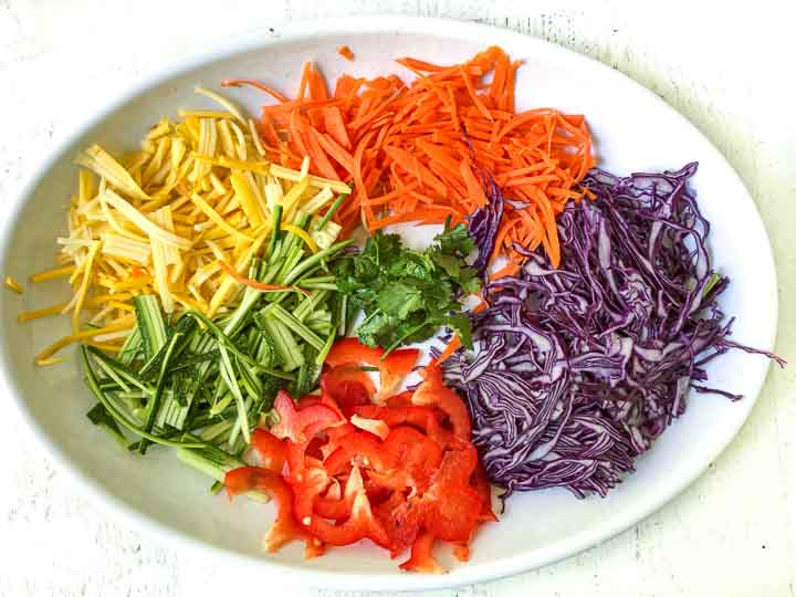white platter with a rainbow of chopped vegetables: purple cabbage, red peppers, orange carrots, yellow zucchini, green zucchini, green cilantro