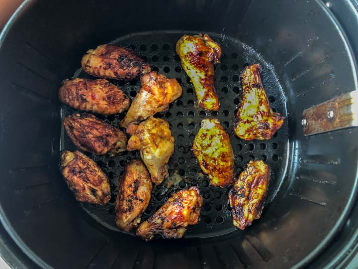 air fryer basket with cooked chicken wings