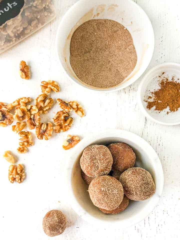 aerial view of white bowl with cinnamon keto cookie dough balls, raw walnuts, bowl of cinnamon and bowl of cinnamon sugar