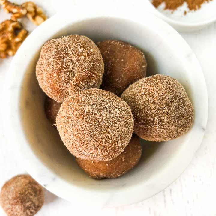closeup white marble bowl with cinnamon sugar covered keto cookie dough balls