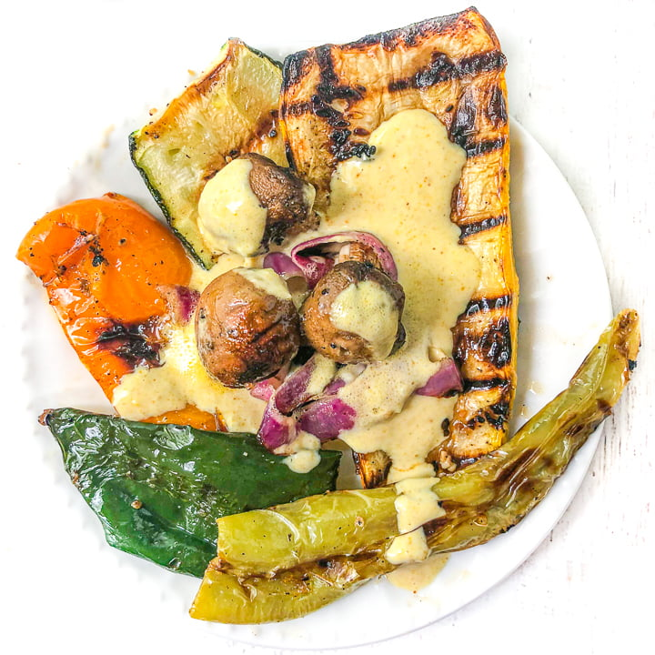 white plate with grilled vegetables with garlic tahini sauce