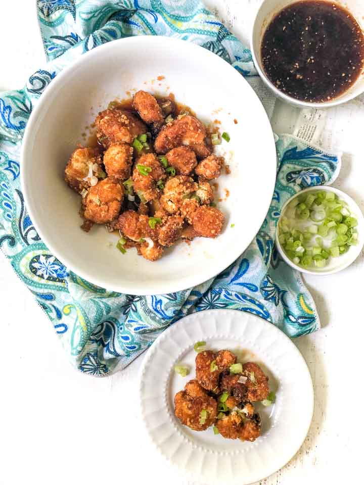 white bowl and plate with keto fried Asian cauliflower with a blue paisley tea towel and a bowl of chopped green onions and a bowl of dipping sauce