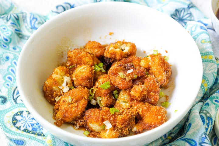 white bowl with air fried cauliflower with asian sauce and green onions with blue tea towel underneath
