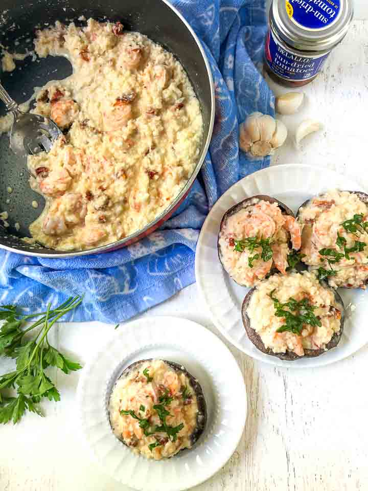 pan with shrimp cauliflower risotto and two white plates with risotto stuffed portobellos with fresh parsley sprigs