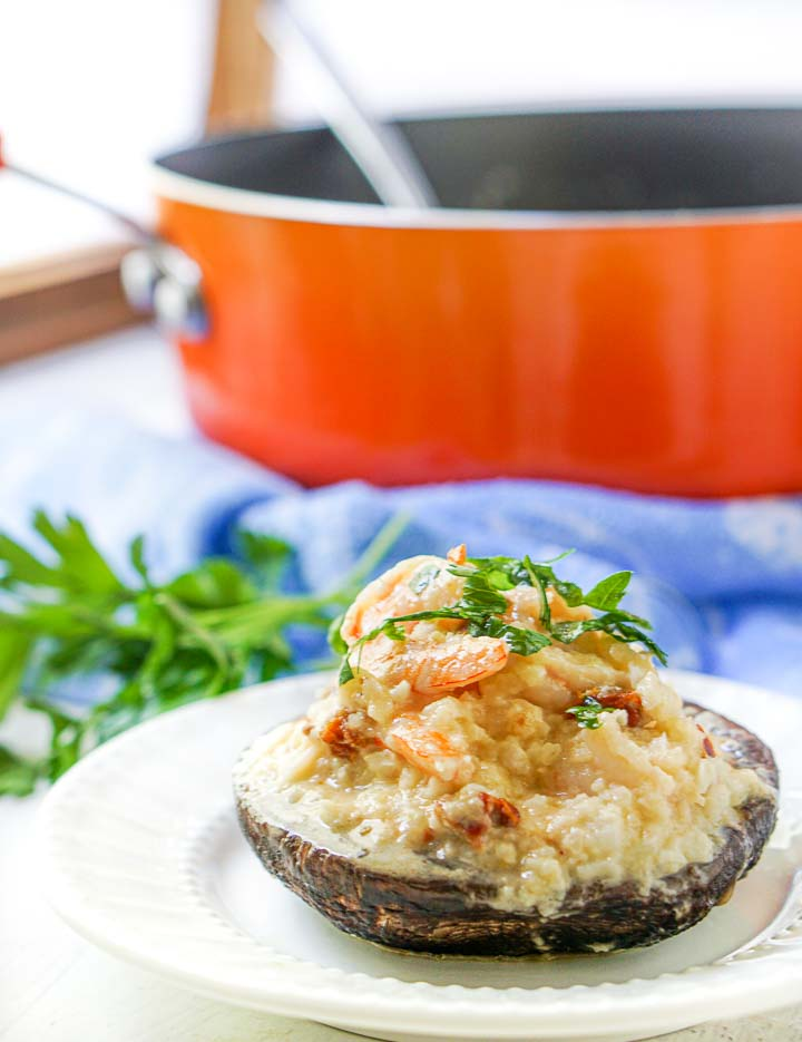 1 shrimp risotto stuffed mushroom cap with an orange pan in background and blue teas towel