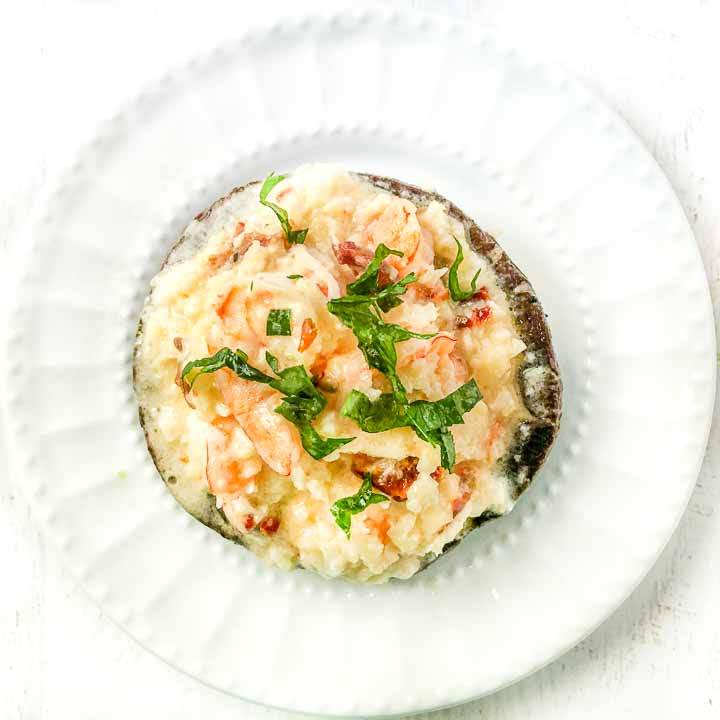white plate with shrimp cauliflower risotto stuffed portobello mushroom