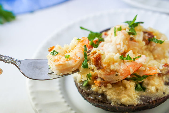 a fork with some risotto and a cooked shrimp