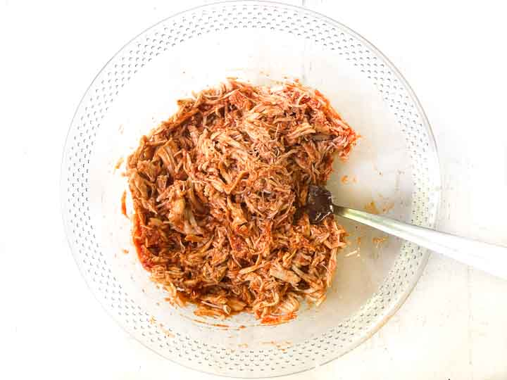 glass bowl with bbq pulled chicken and a fork