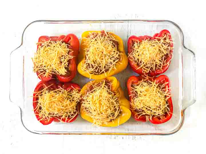 baking dish with yellow and red chicken stuffed peppers ready to be backed