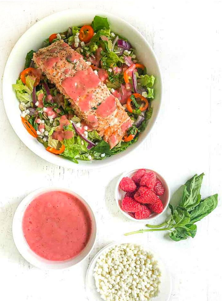 bowl of goat cheese & salmon salad and a bowl of raspberry dressing, a bowl of fresh raspberries and basil and a bowl of goat cheese crumbles