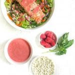 white bowl with low carb goat cheese & salmon salad with raspberry dressing and text