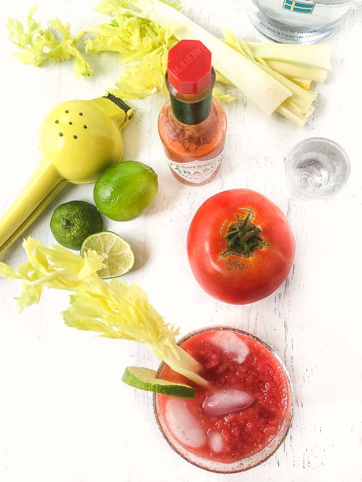 aerial view of a keto Bloody Mary, fresh tomato, celery stalks limes and a shot glass