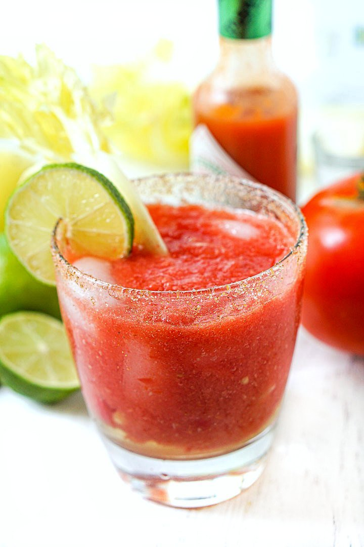 glass of low carb drink with fresh tomatoes, limes and celery and a bottle of tobacco in the background