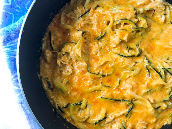closeup of a pan of buffalo chicken zucchini noodles with melted cheddar on top