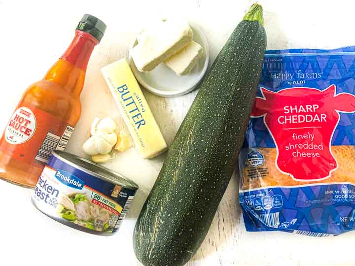 ingredients for recipe: a bottle of hot sauce, garlic cloves, butter, cream cheese, canned chicken, bag of cheddar cheese and raw zucchini