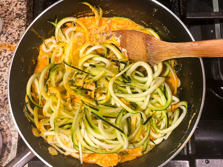 saute pan with buffalo chicken sauce and raw zucchini noodles ready to cook