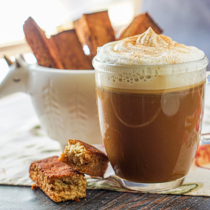 clear glass mug with cinnamon toast coffee with whipped cream and cinnamon and a lama cup with biscotti in it