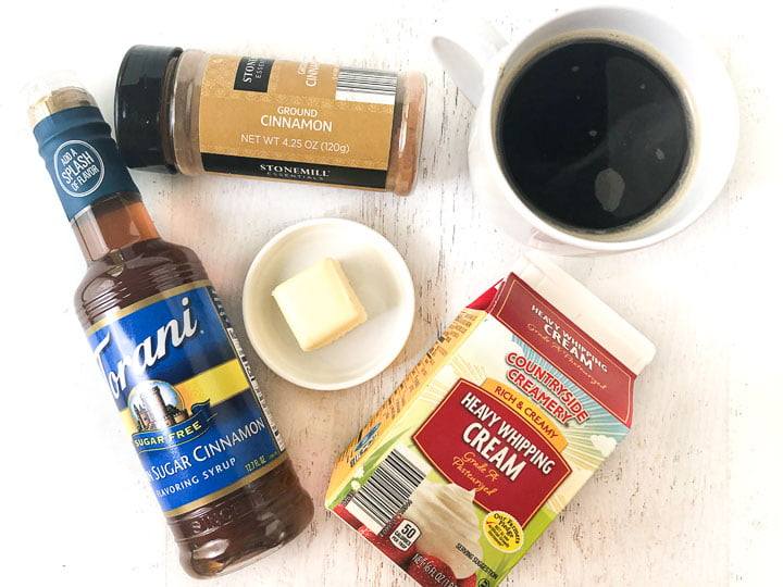 ingredients to make the keto butter coffee: a cup of black coffee, cinnamon, butter, heavy cream and a bottle of Torani syrup