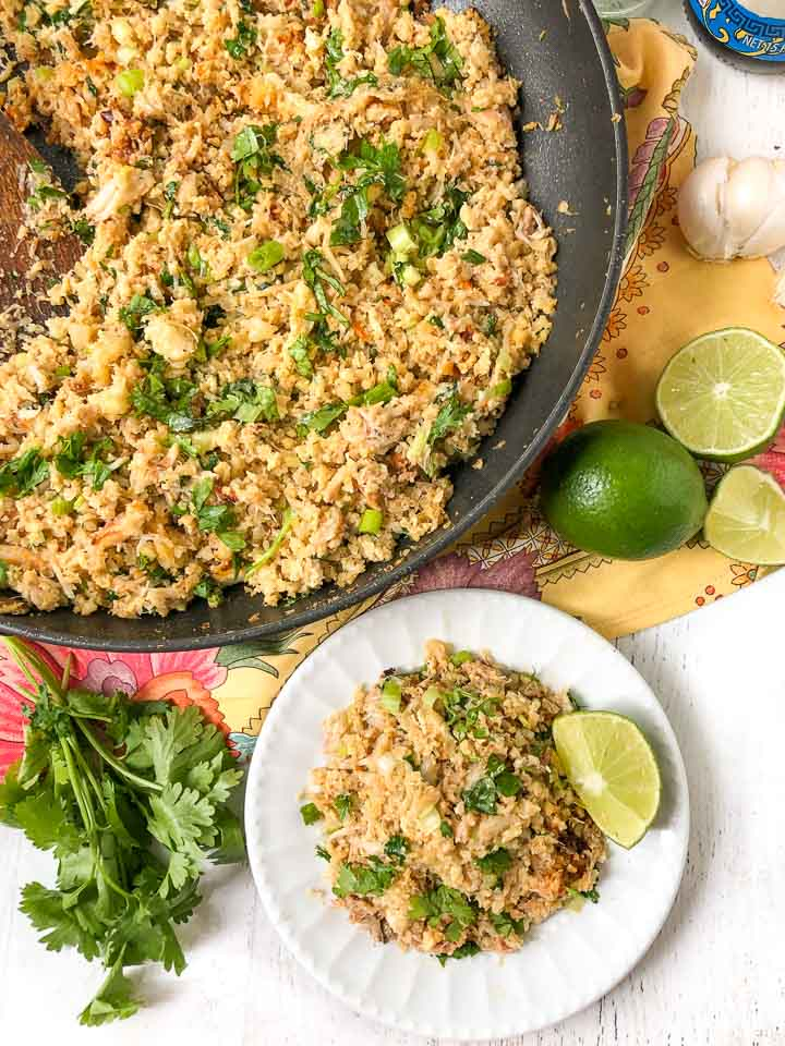 pan and plate with the fried cauliflower rice with a bunch of fresh cilantro and cut limes and a colorful floral cloth beneath