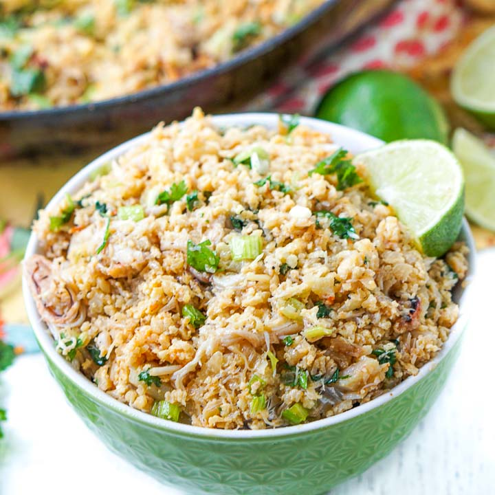 closeup of a green bowl with keto crab fried cauliflower rice a slice of lime