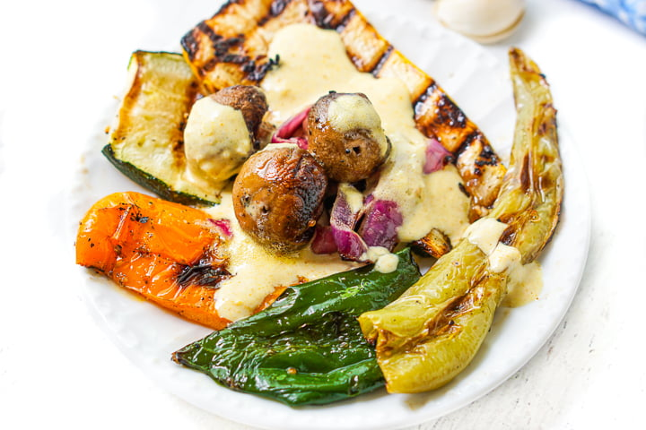 white plate with all of the grilled vegetables topped with tahini sauce