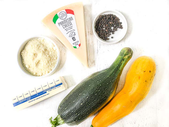 recipe ingredients: green and yellow zucchini, pepper corns, a black of parmesan cheese, grated cheese and butter