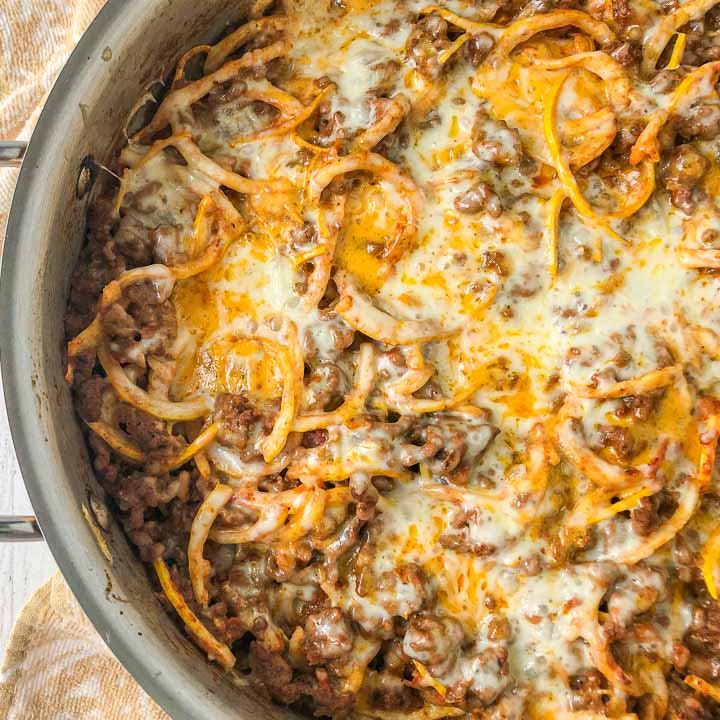 closeup of a pan of keto zucchini noodles in a cheese ground beef tomato sauce