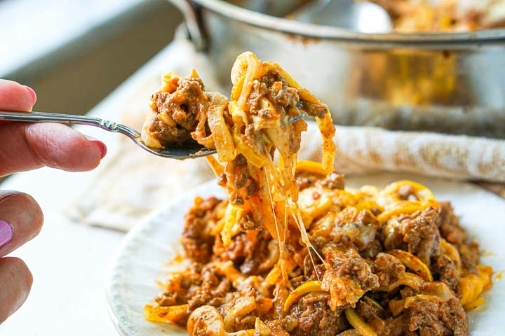 fork full of cheesy, stringy zucchini noodles with ground beef sauce
