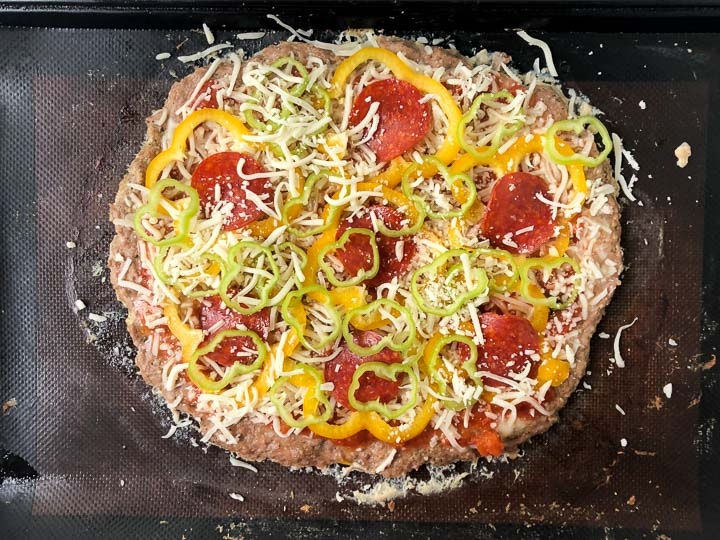 turkey pizza on a cookie sheet after baking and with toppings ready to cook again.