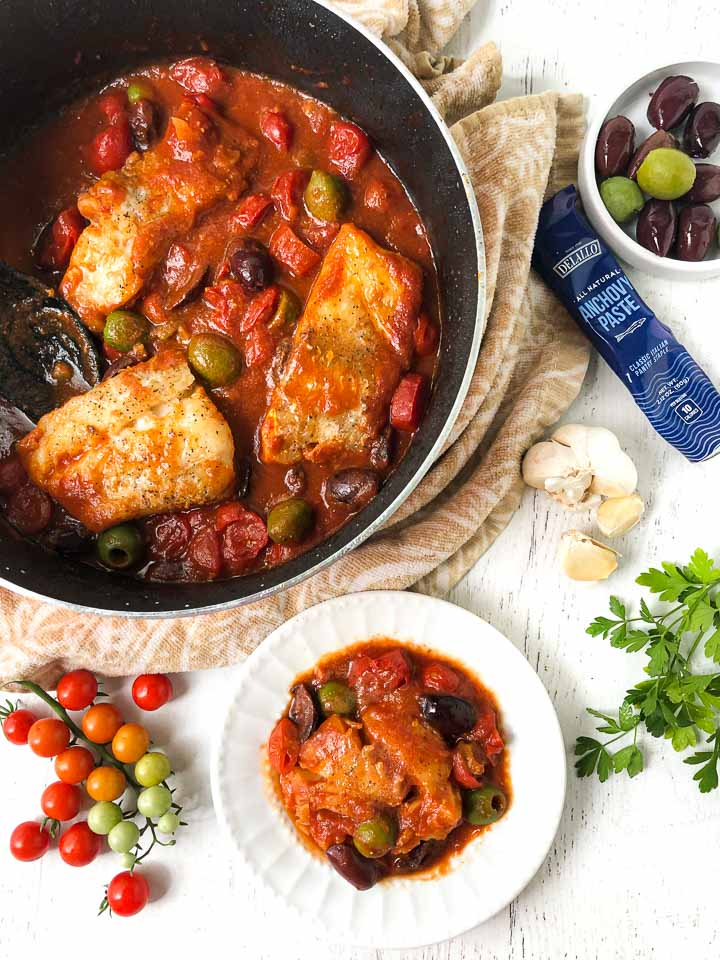white dish and pan with cod with tomato and olive sauce with bowls of olives and anchovy paste and grape tomatoes on the vine