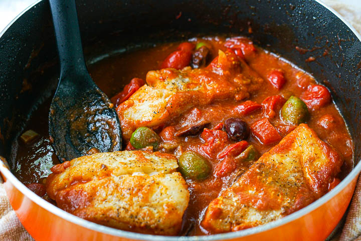 orange pan with cod in  tomato sauce with black spoon