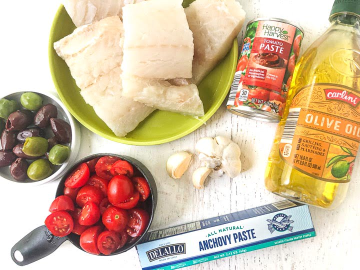 ingredients to make Mediterranean cod: cod filets, Kalamata and green olives, garlic cloves, tomato paste, olive oil, anchovy paste and grape tomatoes