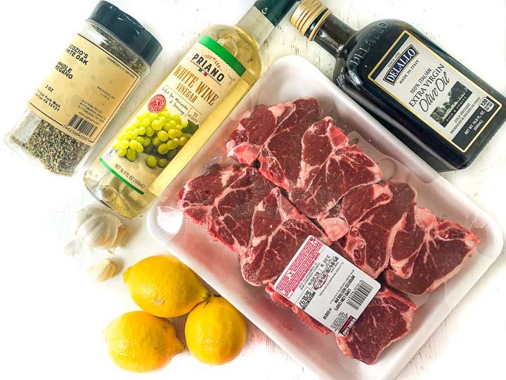 raw lamb chops, olive oil, white wine vinegar, lemons, garlic cloves and oregano