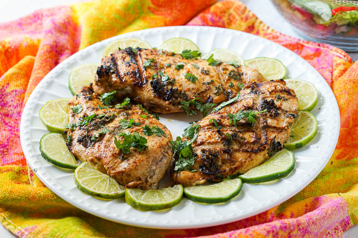white plate with 3 grilled pieces of low carb chicken surrounded by lime slices on a colorful towel