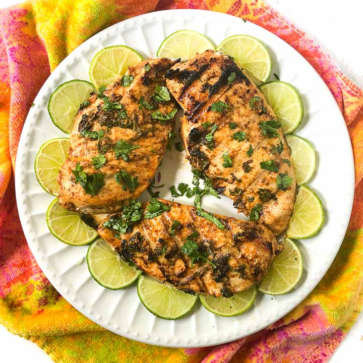 white plate with 3 marinated grilled chicken breasts with lime slices on a colorful tea towel