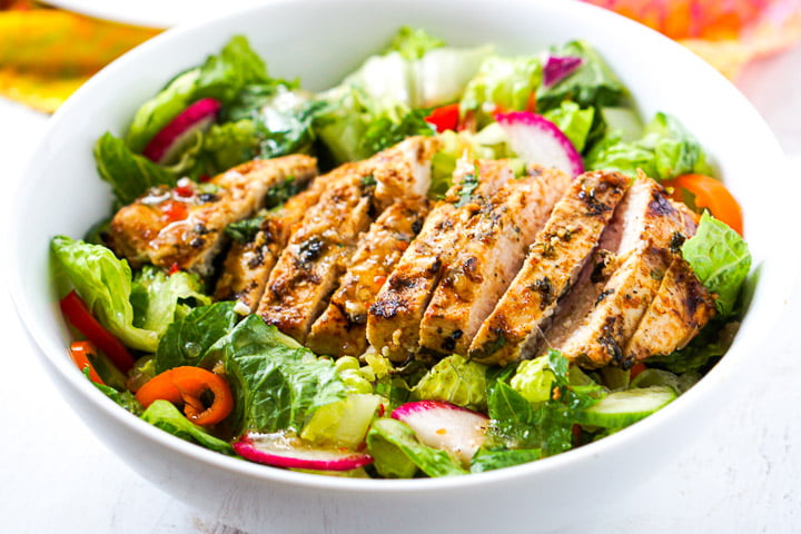 closeup of a white bowl of salad with sliced grilled chicken breast on top