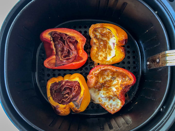 air fryer basket with cooked peppers stuffed with meat and cheese