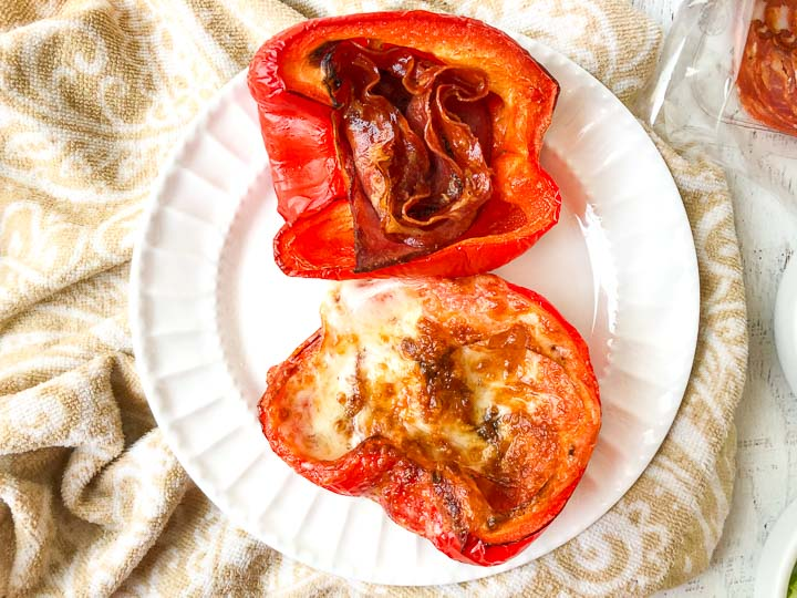cooked red pepper halves on a white plate stuffed with Italian meats and provolone cheese