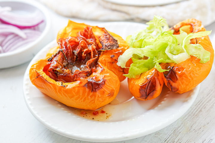 yellow cooked pepper halves with cooked meats and topped with shredded lettuce