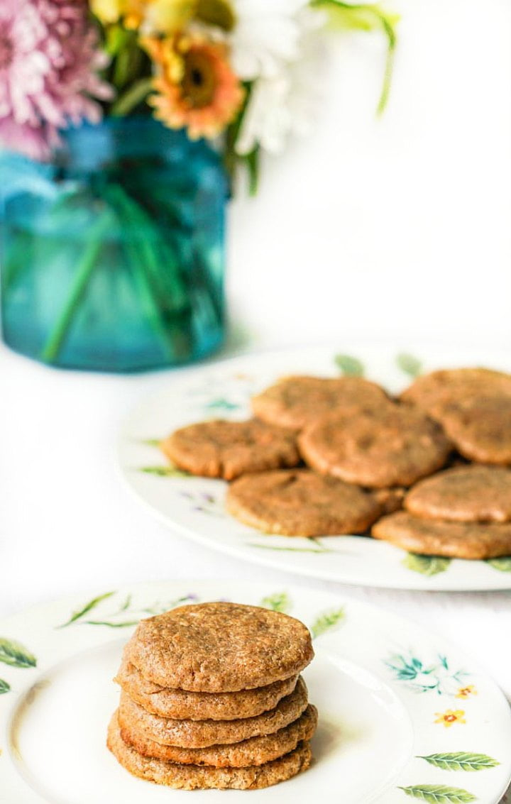 herbal decorated plates with sugar free almond butter cookies and a turquoise vase with flowers in the background
