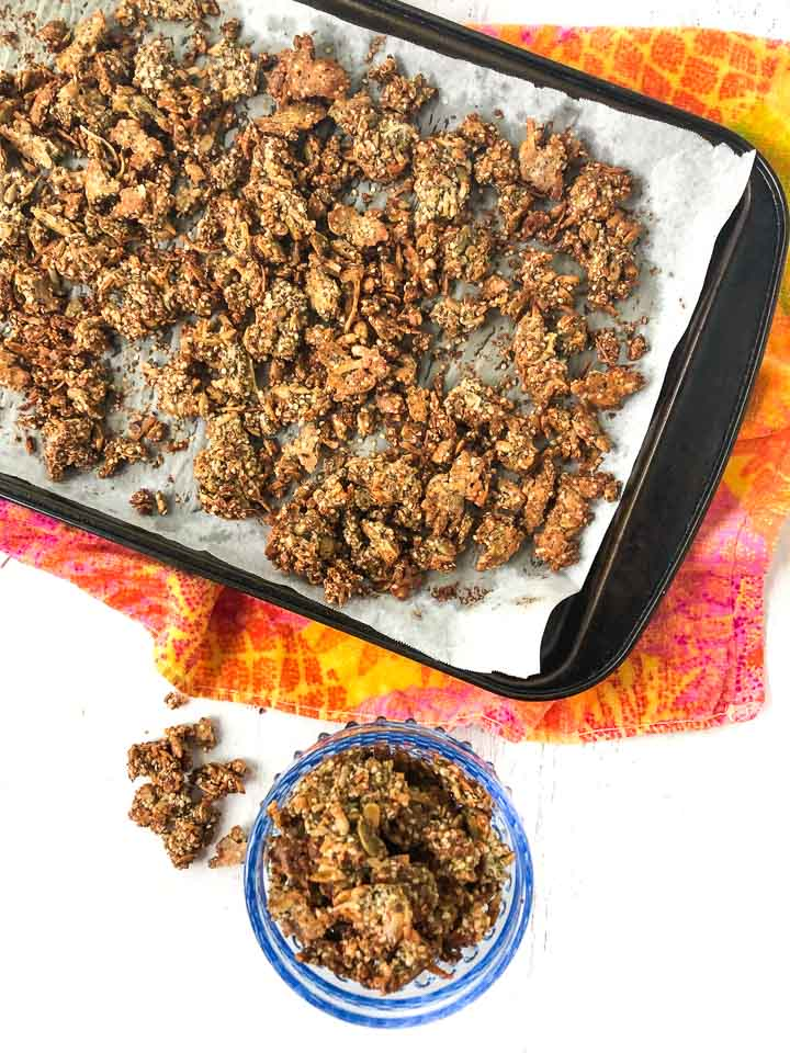 aerial view of a cookie sheet and blue glass bowl of homemade granola on a colorful tea towel