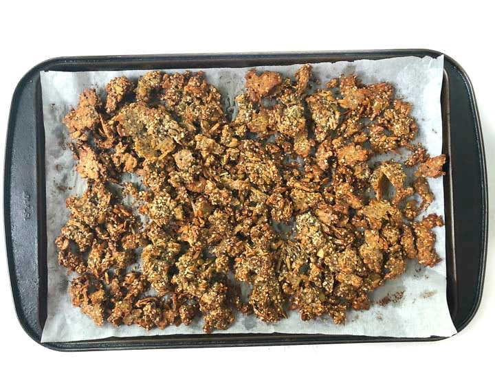 black cookie sheet with parchment paper  with baked banana bread granola