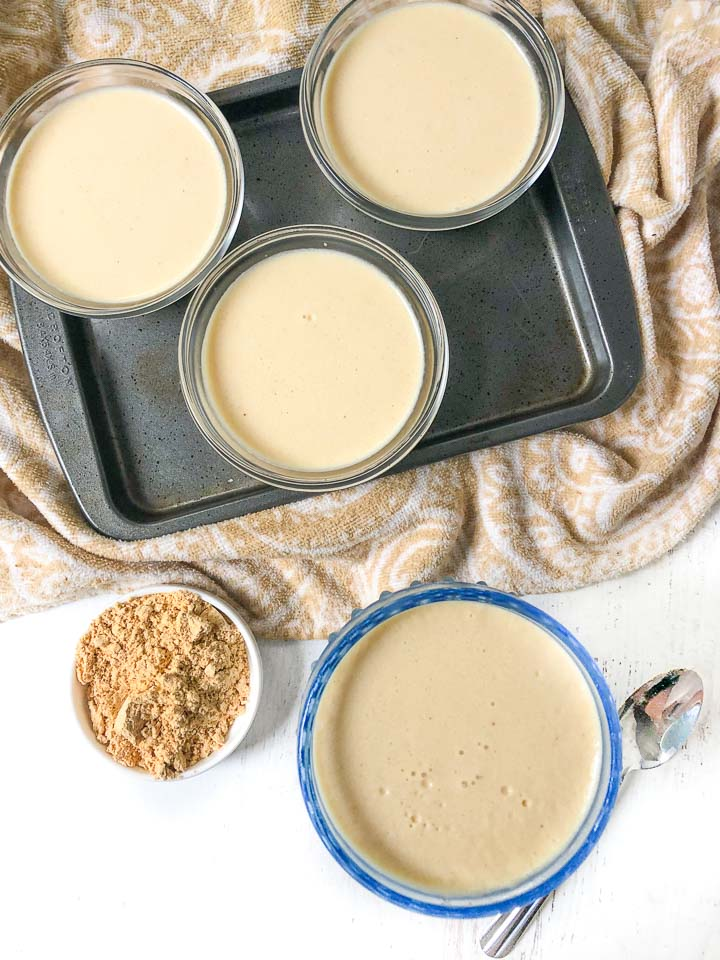 aerial view of small cookie sheet with custard bowls and blue dessert dish filled with sugar free pudding and a bowl of peanut butter powder