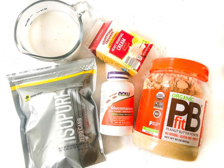 pudding ingredients: isopure banana protein powder, bottle of glucomannan, heavy cream, pitcher of almond milk and PBFit peanut butter powder container