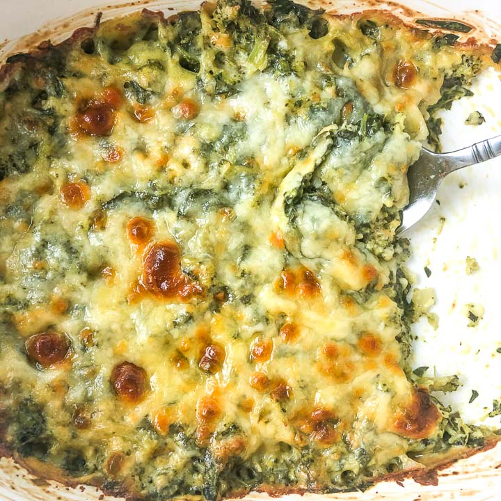 closeup of baking dish with keto spinach and broccoli cheese casserole with a spoon