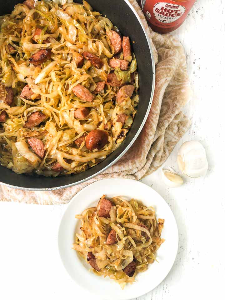 aerial view of a pan and dish with kielbasa and cabbage noodles with garlic cloves and hot sauce