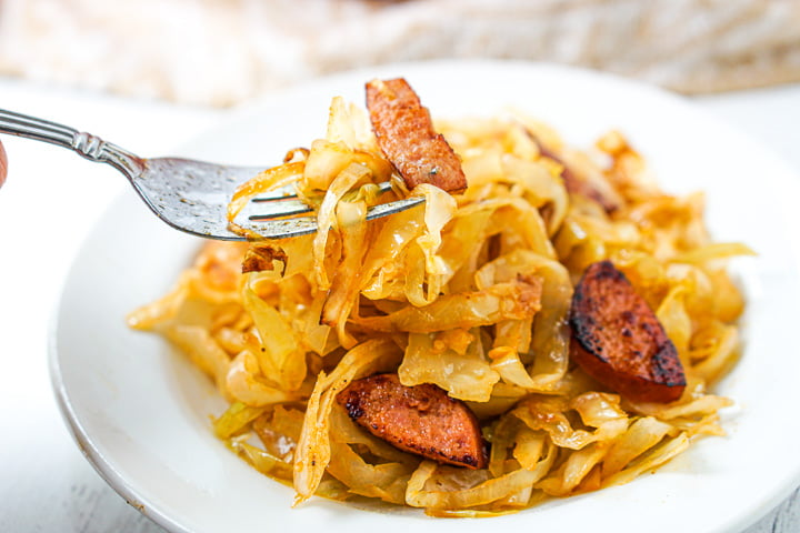 a forkful of cabbage noodles with a piece of kielbasa