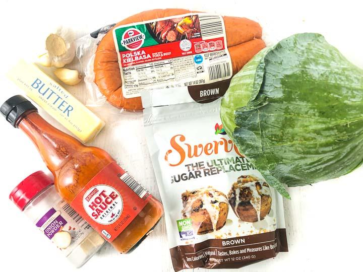 kielbasa recipe ingredients: hot sauce, kielbasa, cabbage, Swerve brown sugar, garlic cloves, butter and onion salt