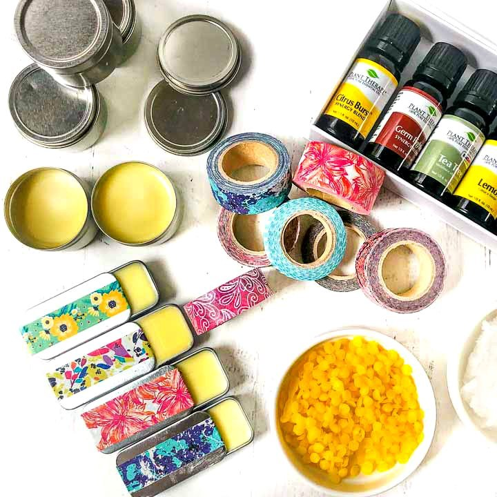 aerial view of homemade lip balm in tins decorated with washi tape, essential oils and beeswax beads