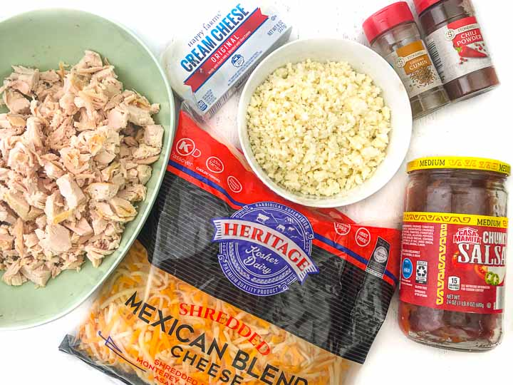 ingredients for Mexican casserole: cauliflower rice, cooked chicken breast, cream cheese, Mexican cheese, salsa, cumin and chili powder